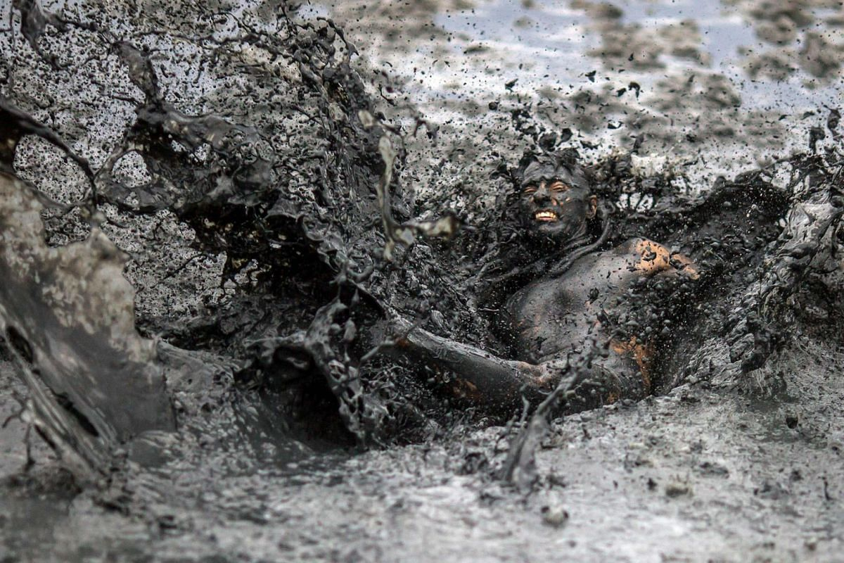 "A reveller jumps on the mud during the ""Bloco da Lama"", a mud carnival party, in Paraty, Rio de Janeiro state, Brazil, on February 22, 2020. PHOTO: AFP"