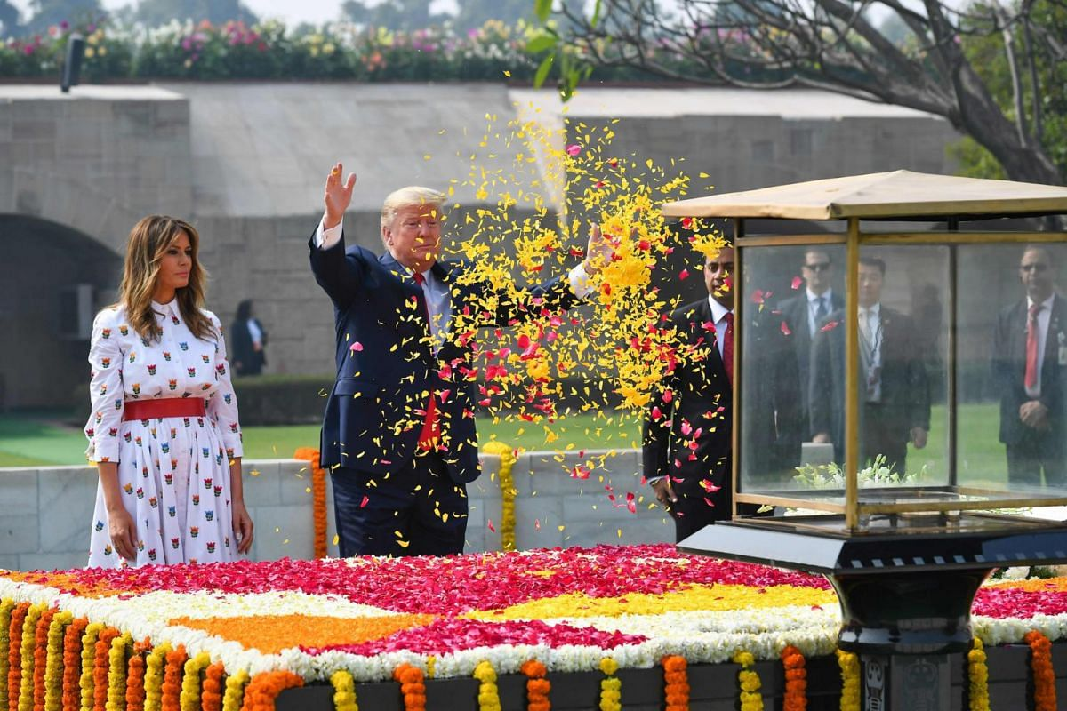 US President Donald Trump sprays flower petals as First Lady Melania Trump looks on while paying their tribute at Raj Ghat, the memorial for Indian independence icon Mahatma Gandhi, in New Delhi, India, on Feb 25, 2020.