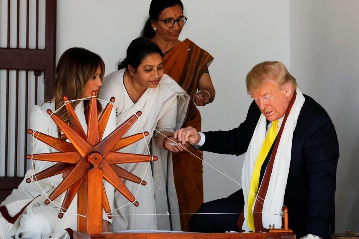 Women show how a Charkha, a type of Indian spinning wheel, works to US President Donald Trump (right) and first lady Melania Trump (left), as they visit the Gandhi Ashram in Ahmedabad, India, on Feb 24, 2020.