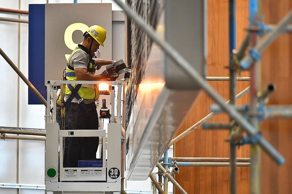 Above: The flip board after it was shut down. The board had been in use at Terminal 2's departure hall since 1999. Right: Site engineer Yazid Yusof, 52, using a scissor lift to remove a capsule from the flip board.