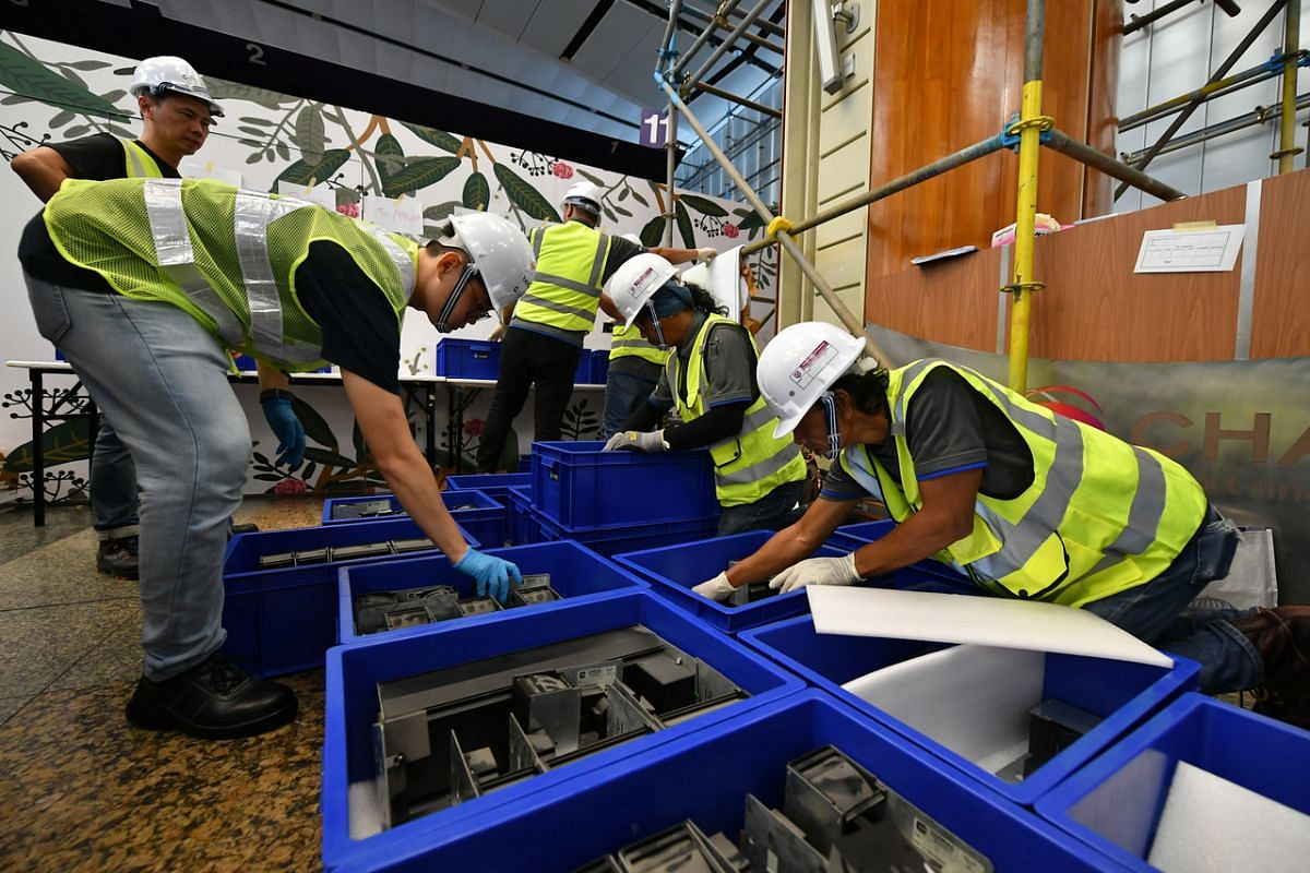 Contractors and National Heritage Board staff packing capsules into containers at Changi Airport Terminal 2 on Feb 13, 2020.