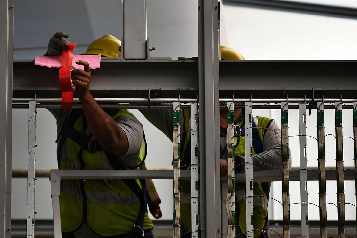 Contractors taping foam on the frame of the first section of the analogue flight information display flip board before hoisting it down at Changi Airport Terminal 2 on Feb 21, 2020.