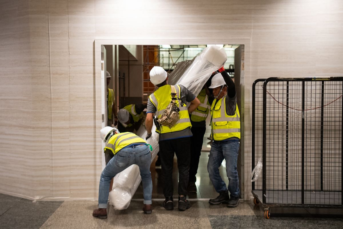 Contractors transferring one of the last six pieces of the holding structure of the analogue flight information display flip board out of the hoarding area in Changi Airport Terminal 2 for loading onto a truck for transportation to a storage facility