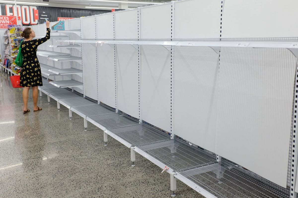 A customer walks past empty toilet paper shelves at a supermarket in Sydney on March 4, 2020.