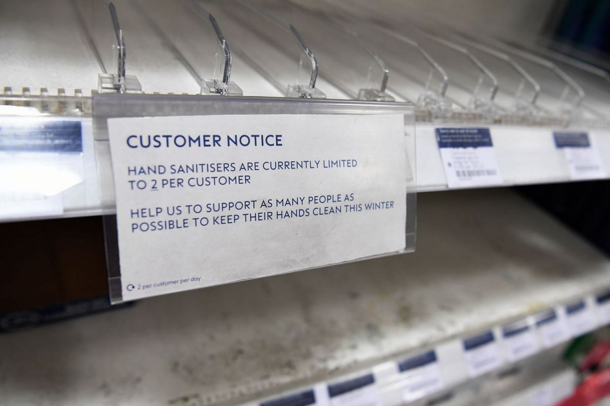 An empty store shelf displays a sign asking customers to limit their purchase of hand sanitisers to 2 per person at a shop in London on March 3, 2020.