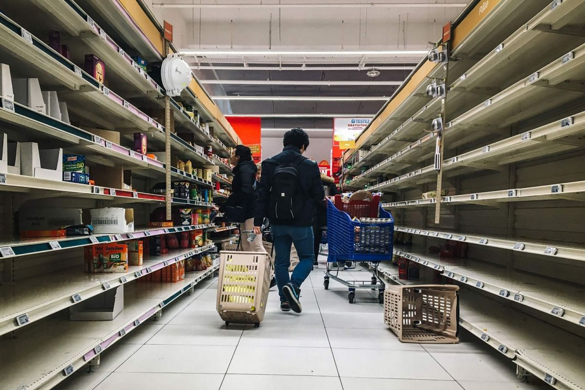 A man pulls a shopping trolley near empty stalls in a supermarket in the Qwartz shopping centre in Villeneuve-la-Garenne, north of Paris, on March 2, 2020.