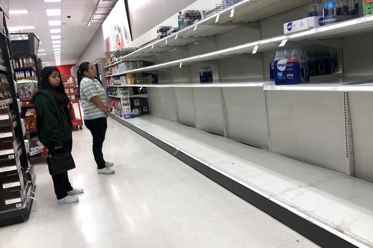 Customers look at empty shelves that usually have bottled water at a Target store in San Rafael, California, on March 2, 2020.