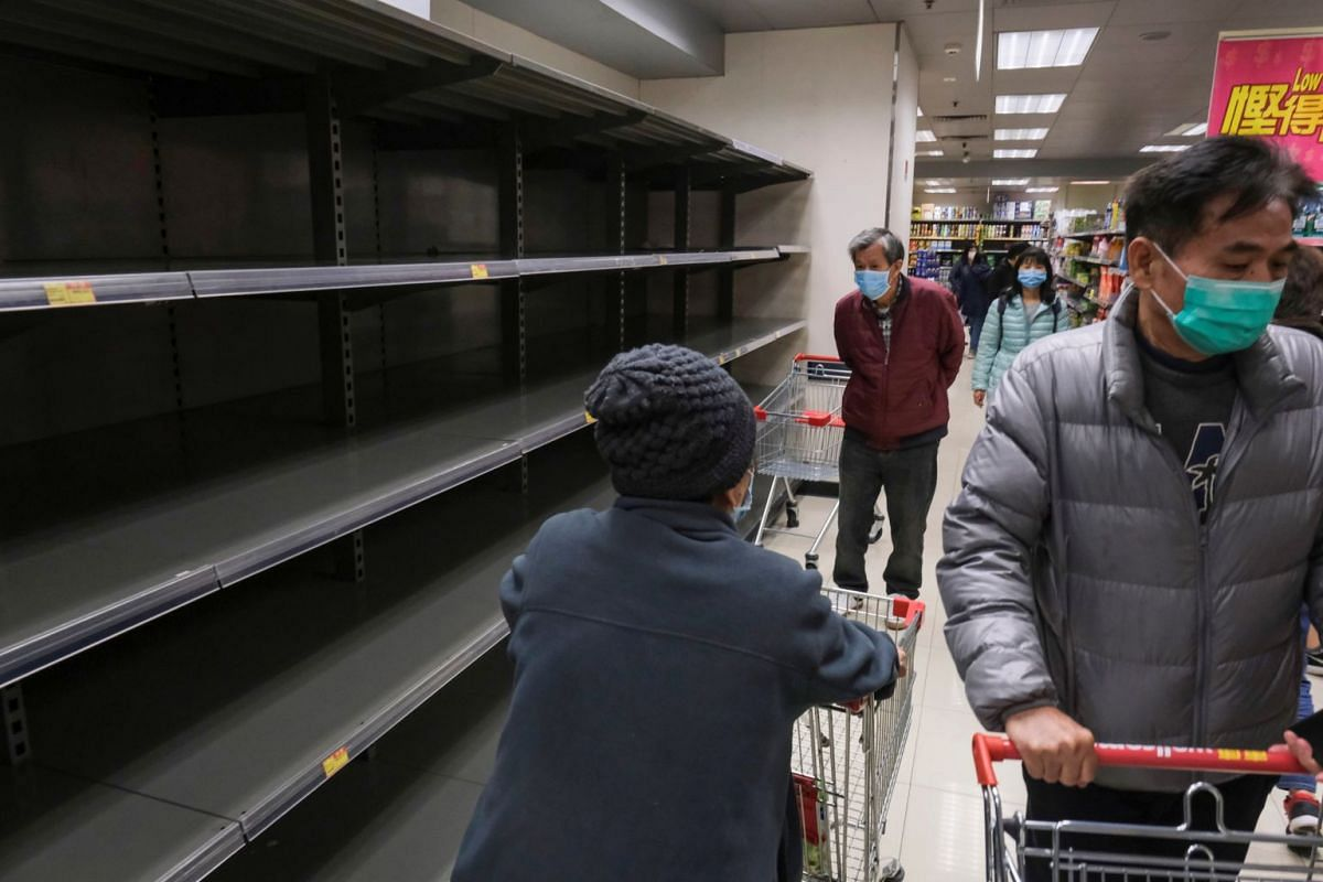 Customers wear masks as they walk past empty toilet paper shelves at a supermarket, following the outbreak of the coronavirus, in Hong Kong, on Feb 6, 2020.
