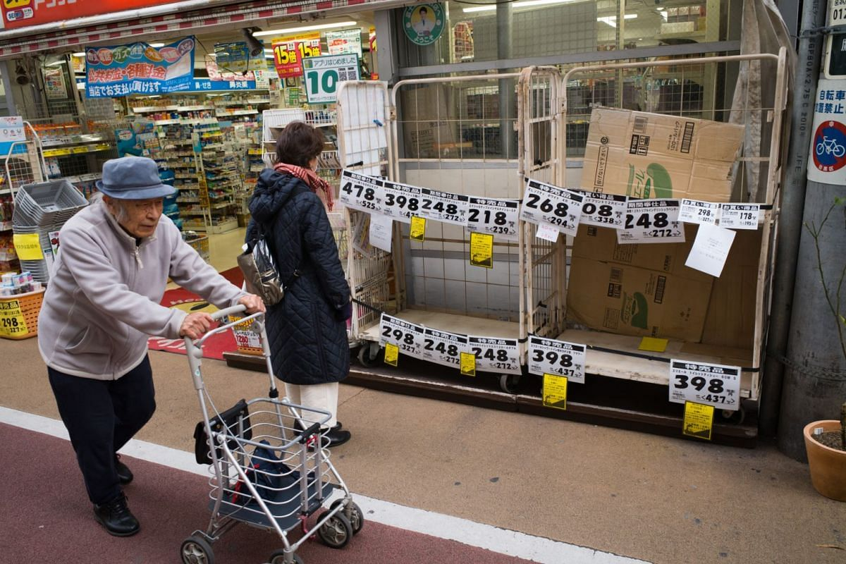 A pedestrian looks at carts displaying notices indicating that sanitisation products are sold out outside a drug store in Tokyo, Japan, on Feb 28, 2020.