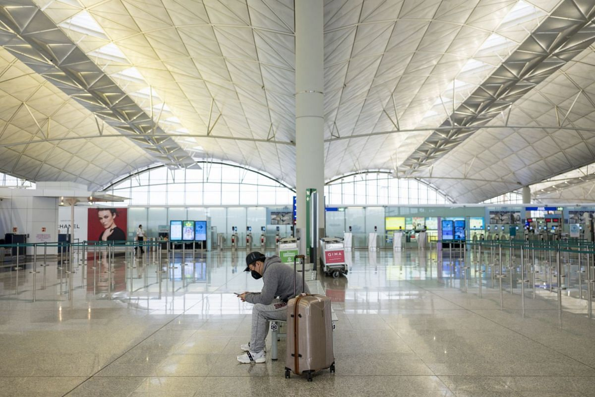 A traveller wearing a mask sits in a near-empty check-in hall at Hong Kong International Airport on March 5, 2020.