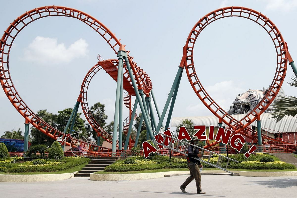 A worker walking past an empty amusement ride at a deserted amusement and water park in Bangkok on March 3, 2020.
