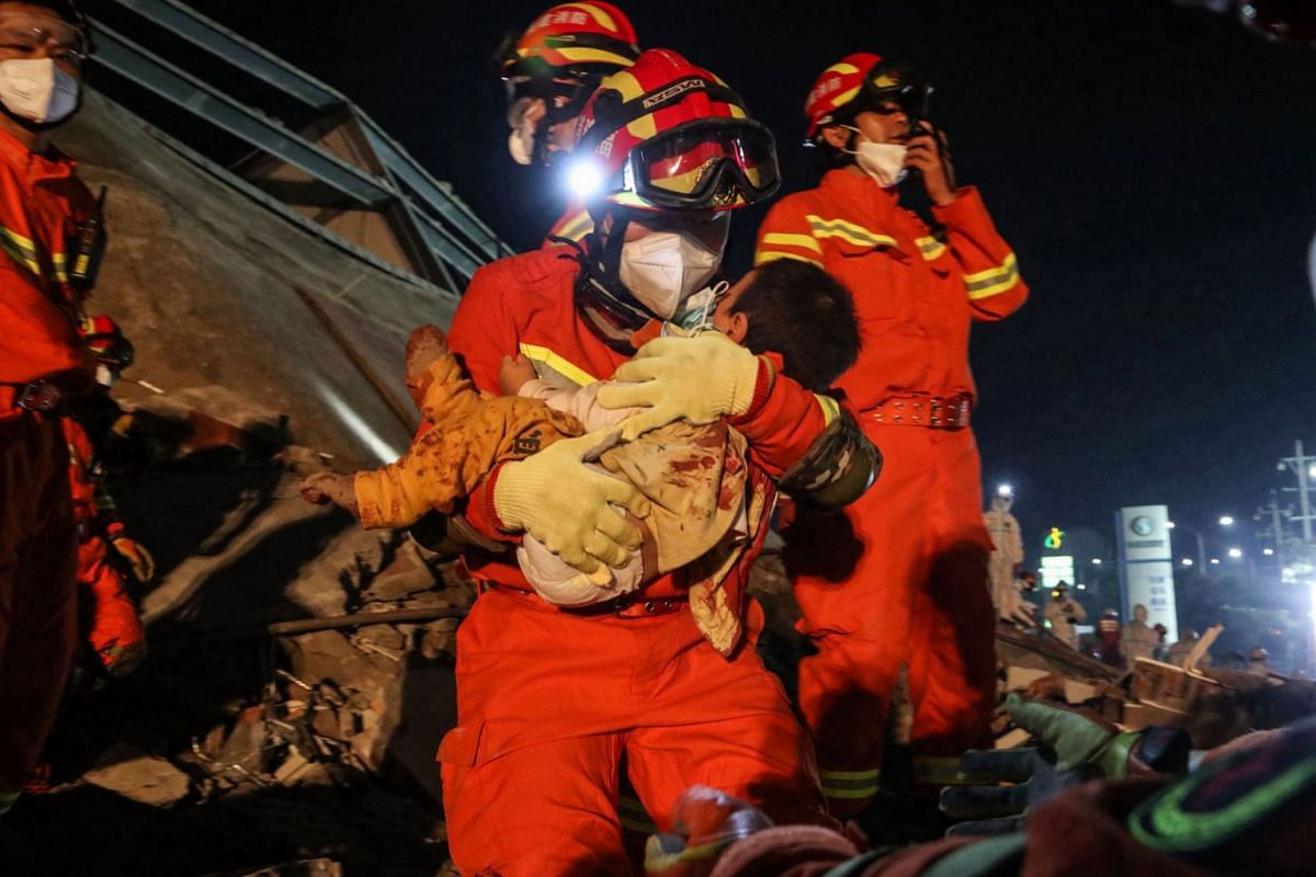 A boy is rescued from the rubble of a collapsed hotel in Quanzhou, in China's eastern Fujian province early on March 8, 2020. At least four people were killed following the collapse of a hotel used as a coronavirus quarantine facility in eastern Chin