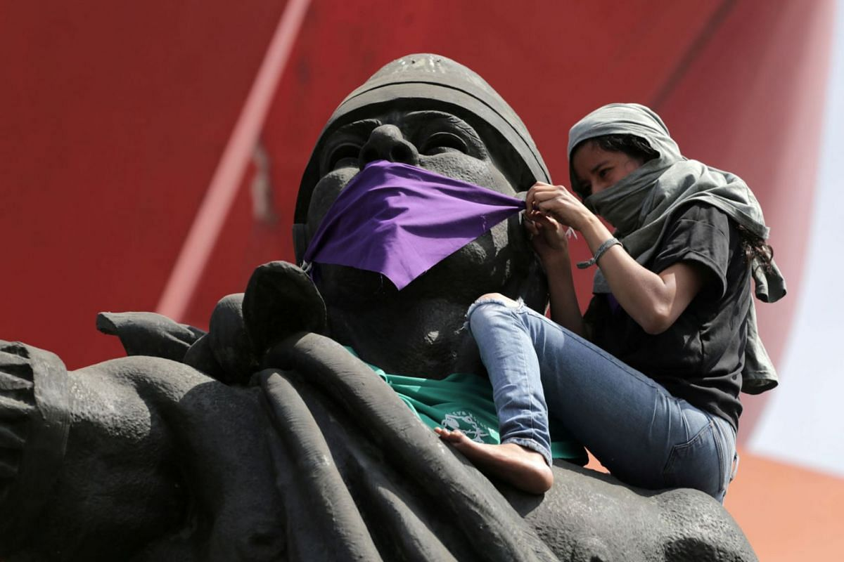 A woman ties a handkerchief over the mouth of the statue of pre-Columbian ruler Nezahualcoyotl, during International Women's Day in Ciudad Nezahualcoyotl, on the outskirts of Mexico City, Mexico March 8, 2020. PHOTO: REUTERS