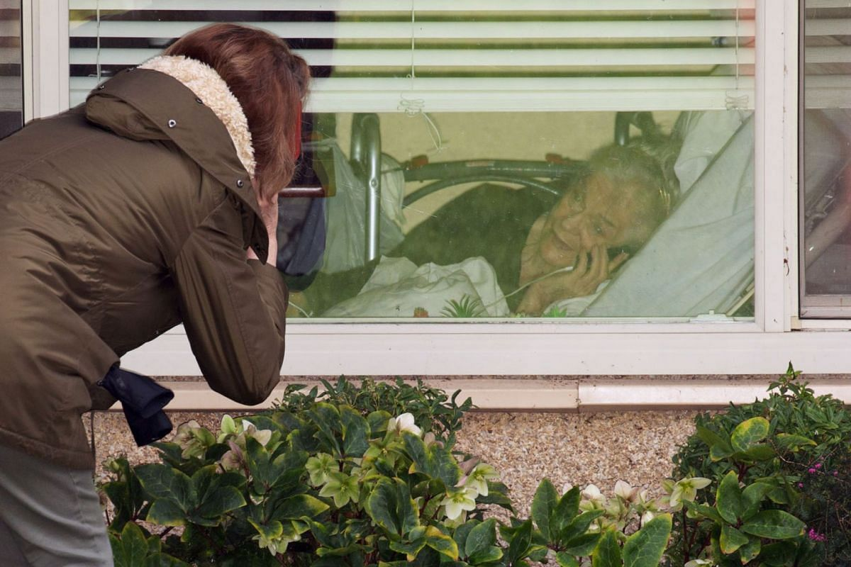 Lori Spencer talks on the phone through a window with her mother, Judie Shape, who is 81 and was tested for coronavirus this morning, at the Life Care Center of Kirkland, the long-term care facility linked to several confirmed coronavirus cases in th