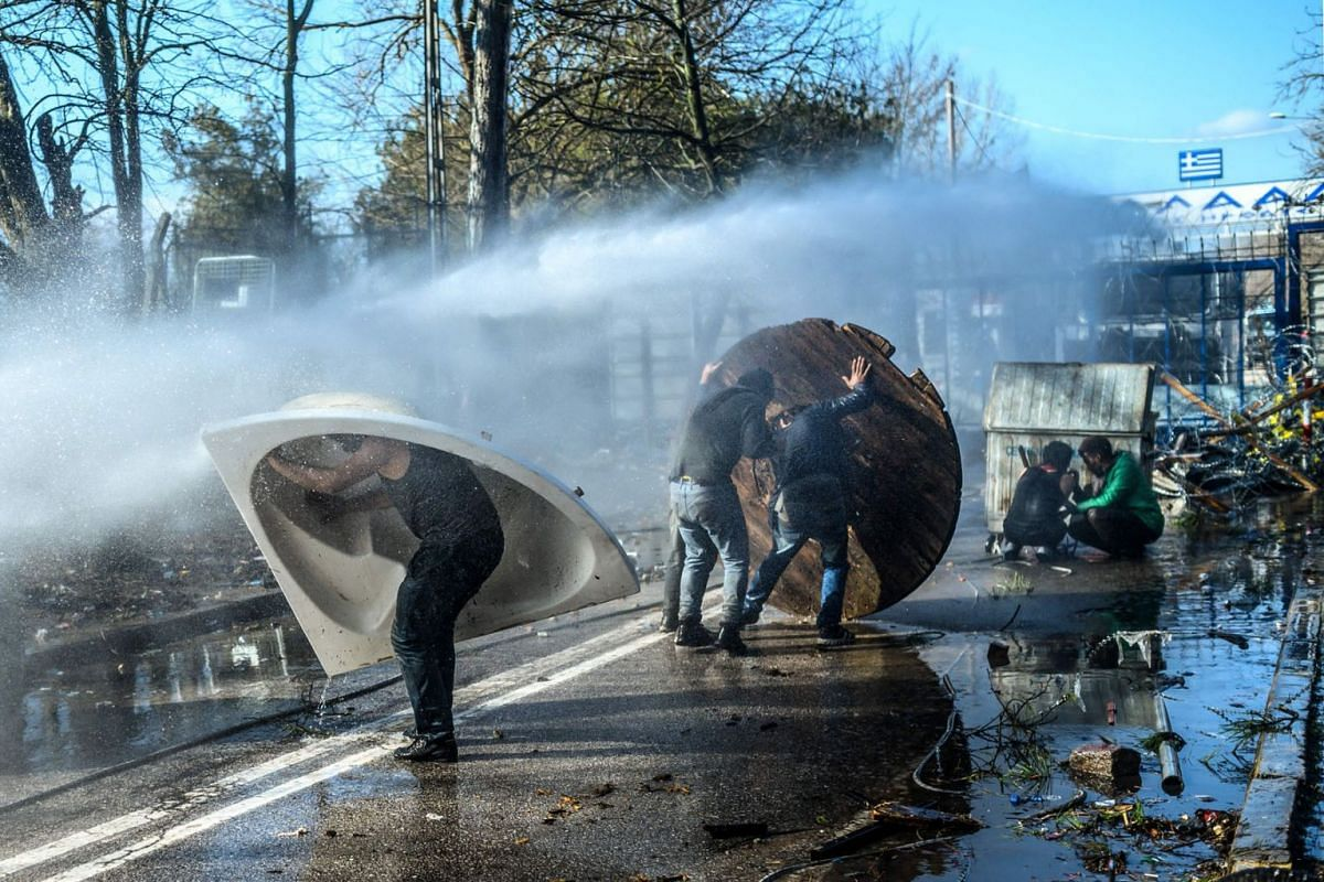 Migrants takes cover behind a trash container, a bathtub and a wooden board as Greek police uses water cannons to block them trying to break fences in the Turkey-Greece border province of Edirne on March 7, 2020. PHOTO: AFP