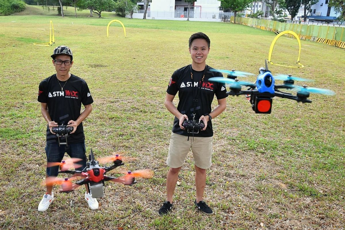 Dance-studio owner Felix Huang (far left) and software developer Ryan Tan with their drones.