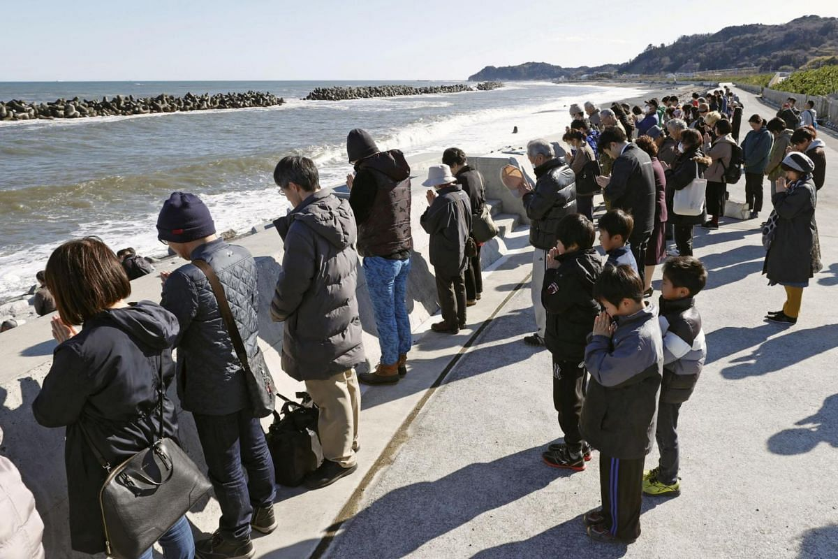 People attend a moment of silence at 2.46pm, the time when the magnitude 9.0 earthquake struck off Japan's coast in 2011, in Iwaki, in Japan's Fukushima prefecture, on March 11, 2020.