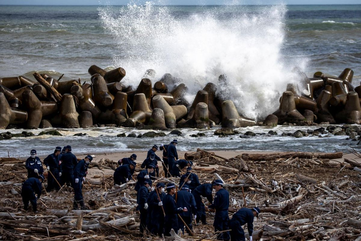 Police officers take part in a search operation for the remains of people who went missing after the March 11, 2011 earthquake and tsunami disaster in Namie, in Japan's Fukushima prefecture, on March 11, 2020.