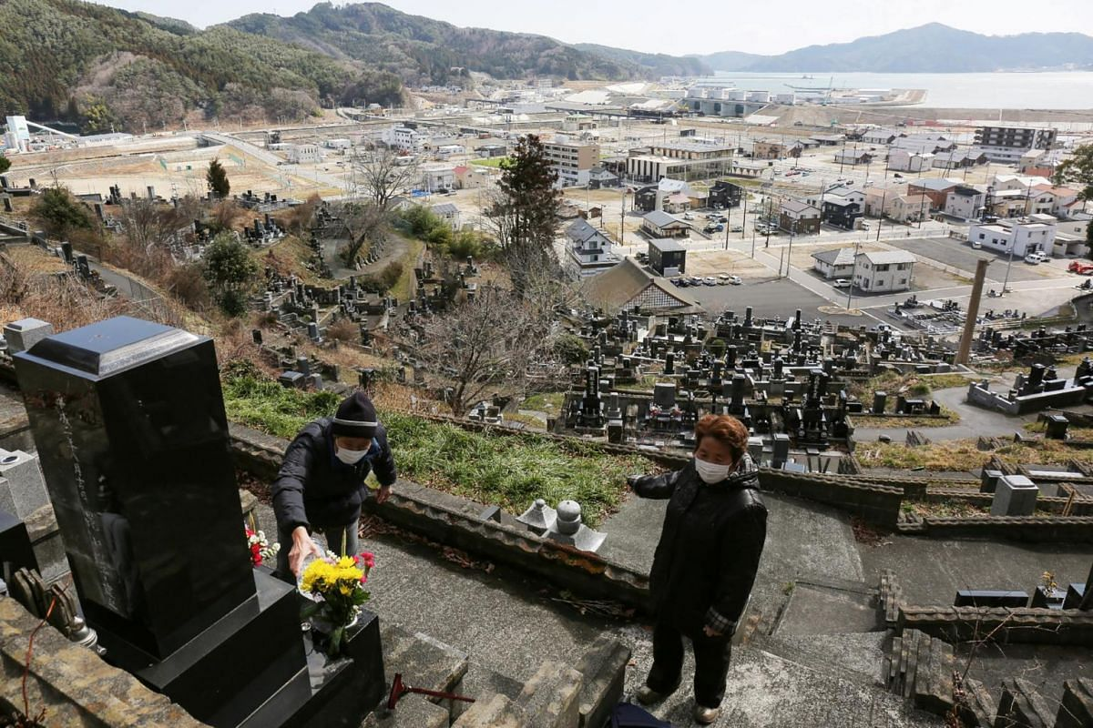 People lay flowers on their relatives' graves at a cemetery in Otsuchi, in Japan's Iwate prefecture, on March 11, 2020, on the ninth anniversary of the 2011 tsunami disaster.