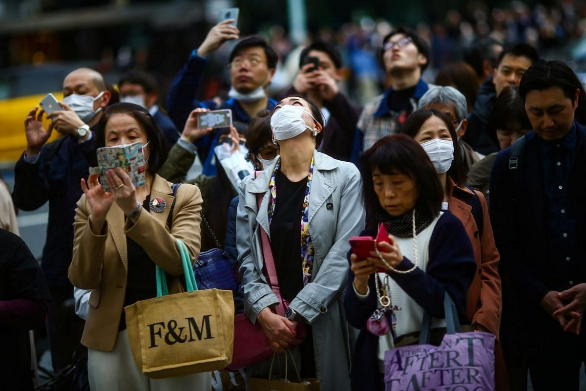 People taking part in a moment of silence at 2.46pm, the time when the magnitude 9.0 earthquake struck off Japan's coast in 2011, in Iwaki, in Japan's Fukushima prefecture, on March 11, 2020.
