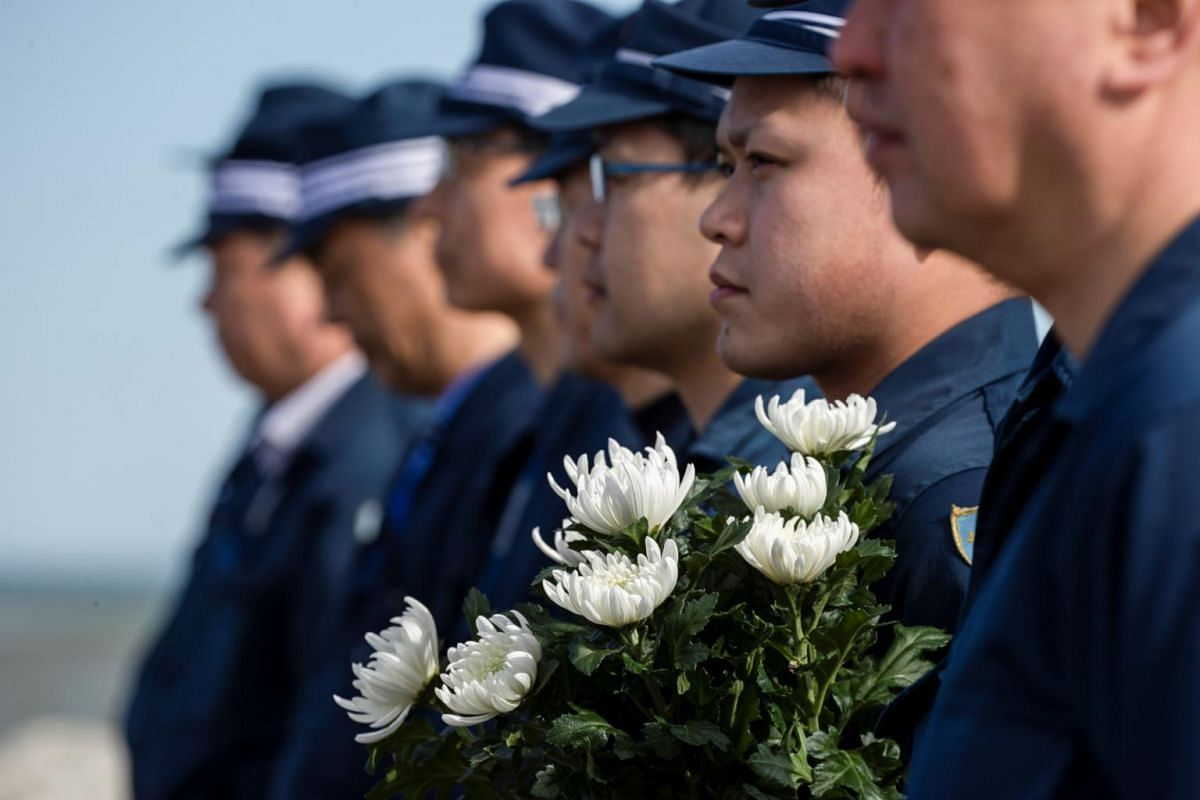 Police officers take part in a moment of silence at 2.46pm, the time when the magnitude 9.0 earthquake struck off Japan's coast in 2011, in Iwaki, in Japan's Fukushima prefecture, on March 11, 2020.