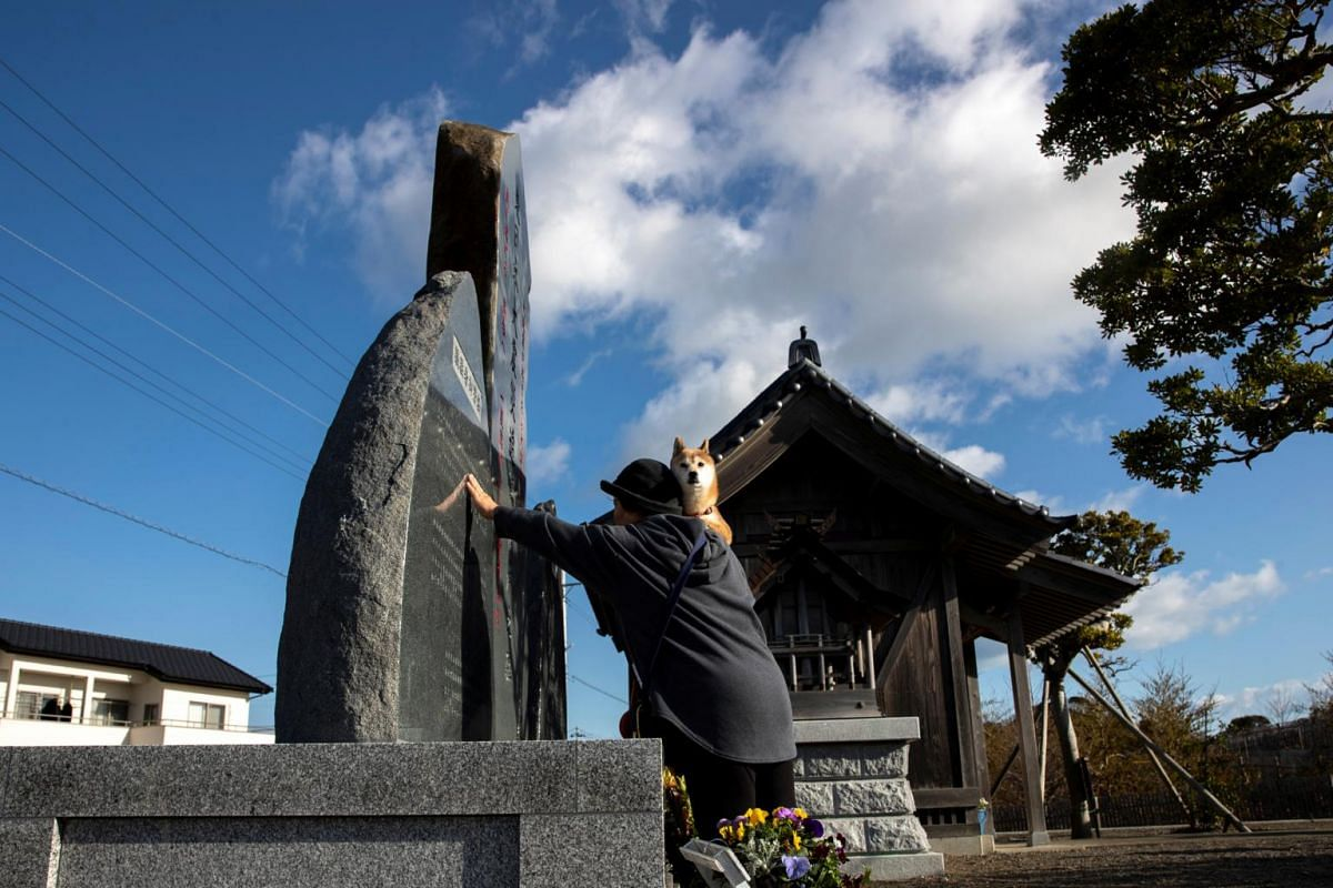 A woman pays her respects to victims of the 2011 tsunami disaster, in Iwaki, in Japan's Fukushima prefecture, on March 11, 2020.