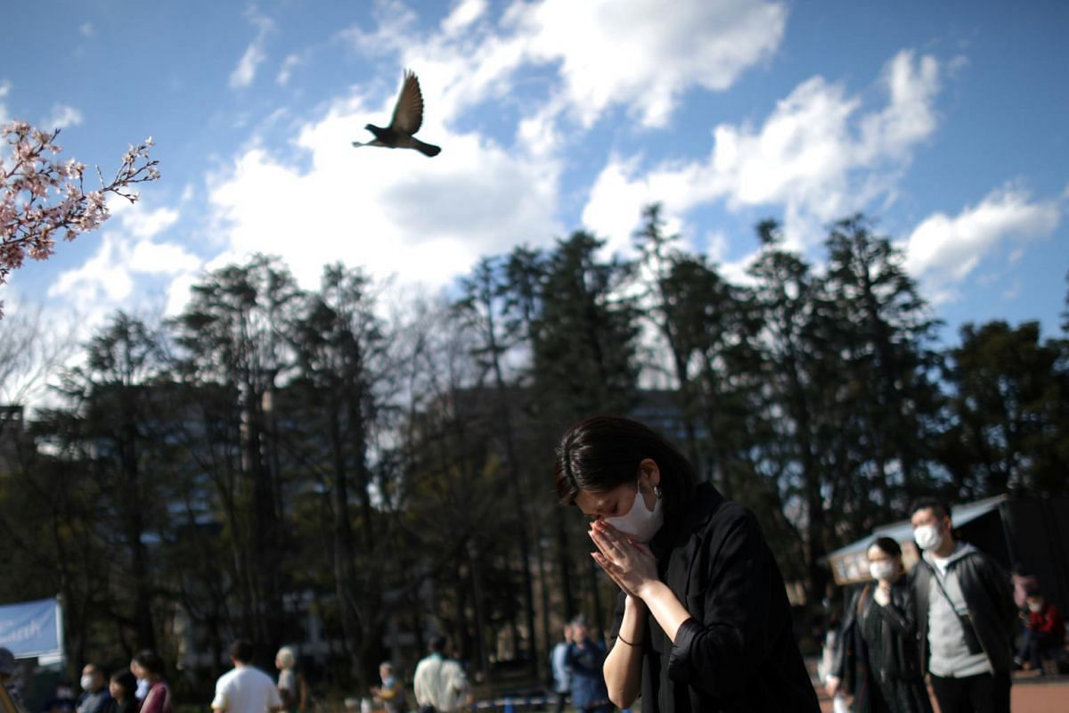 A woman prays during a memorial service preceding a moment of silence at Hibiya Park in Tokyo on March 11, 2020.
