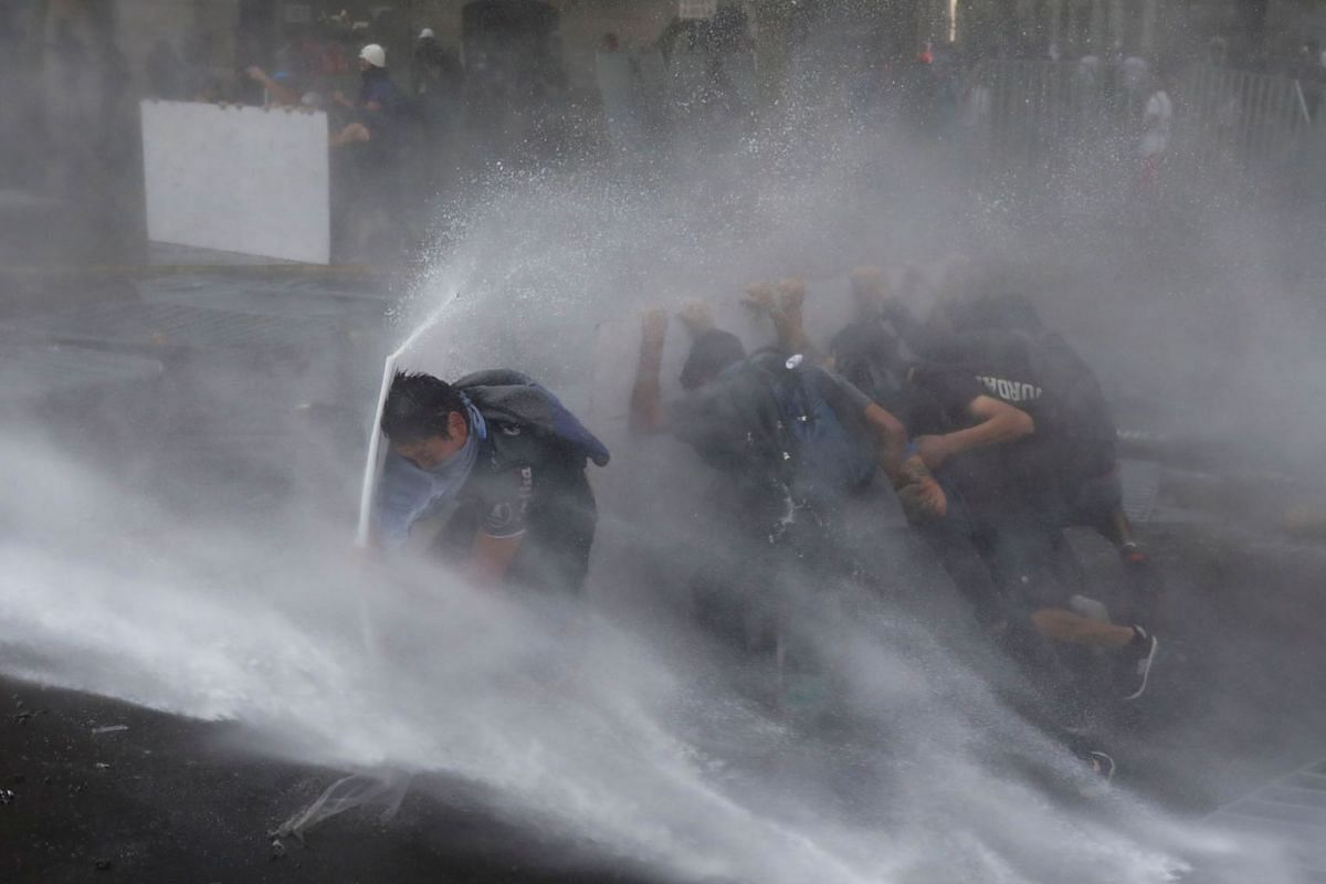 Demonstrators take cover from a water cannon during a protest against Chile's government in Santiago, Chile March 11, 2020. PHOTO: REUTERS