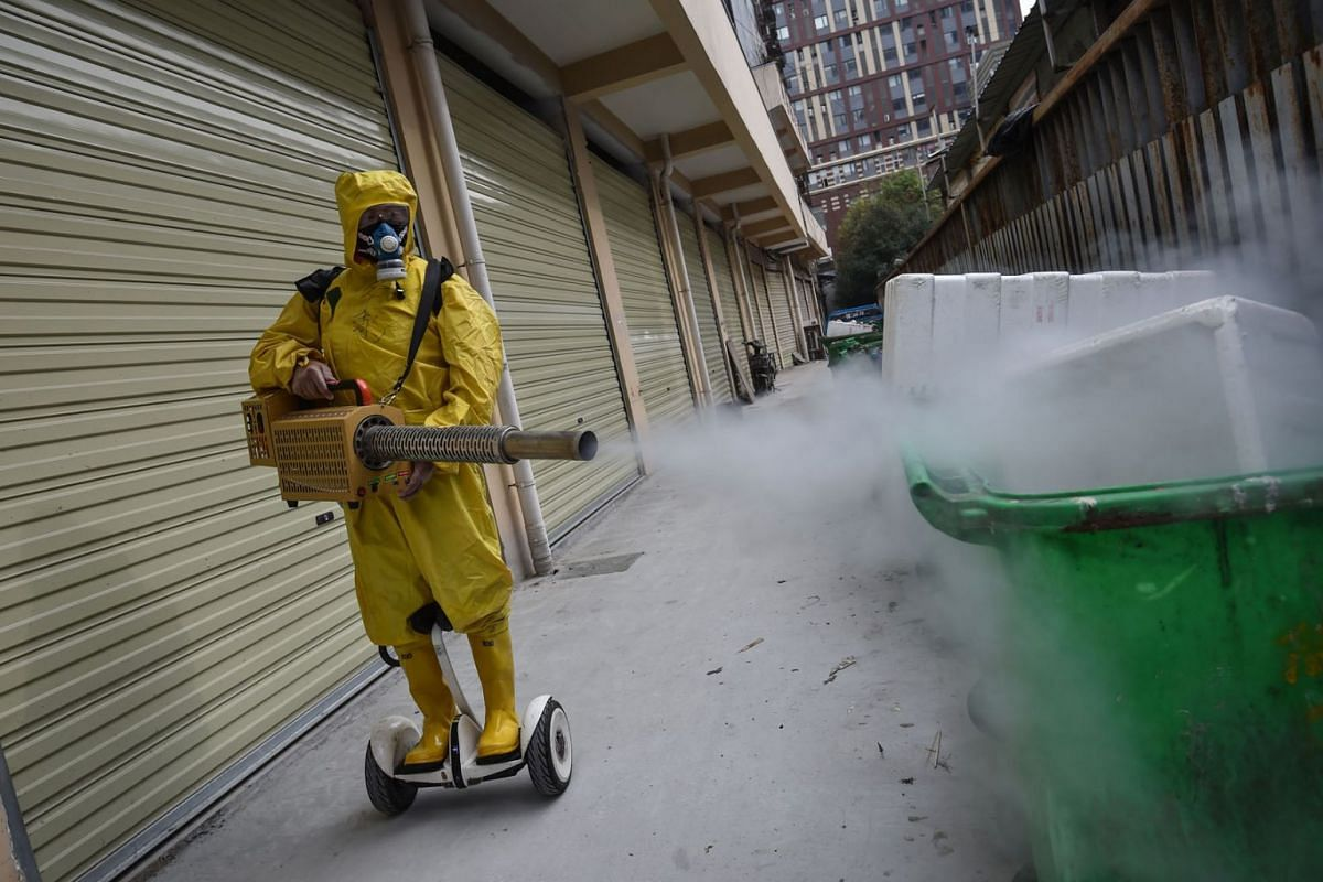 A medical staff member sprays disinfectant at a residential area in Wuhan in China's central Hubei province on March 11, 2020. PHOTO: AFP