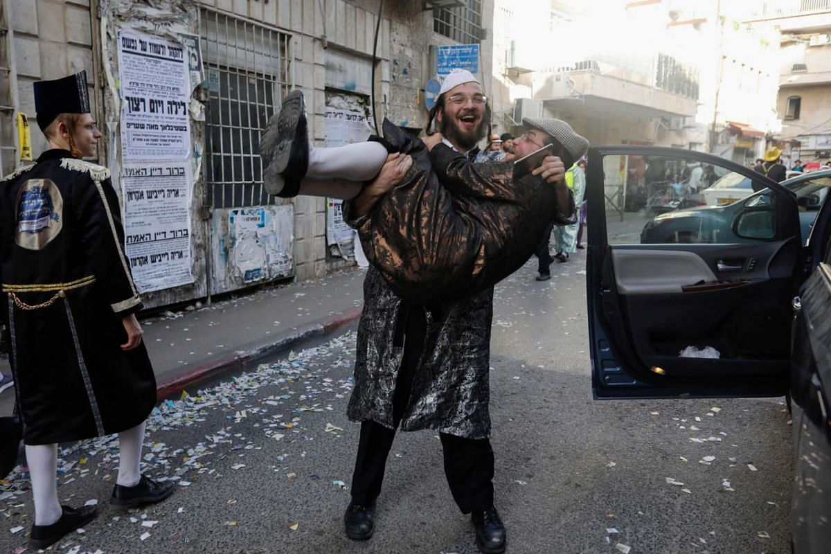 An Ultra-Orthodox Jewish man carries another as they celebrate, dressed in costumes, the feast of Purim in the Mea Shearim Ultra-Orthodox neighbourhood in Jerusalem on March 11, 2020. PHOTO: AFP