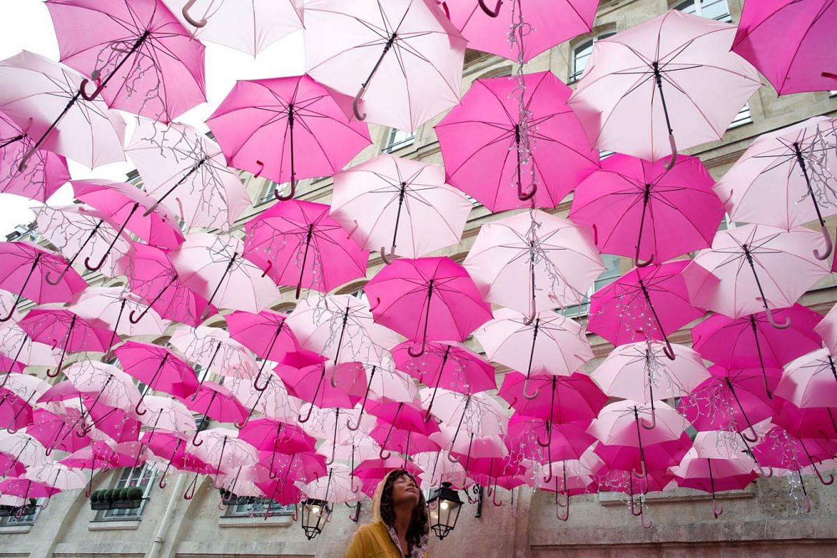 """An installation entitled """"Umbrella Sky Project"""" created by Portuguese artist Patricia Cunha and composed with pink umbrellas is pictured in Paris, France, March 11, 2020. PHOTO: REUTERS"""