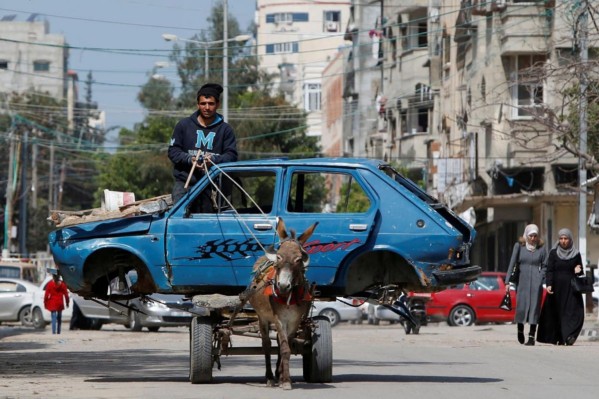 A Palestinian man rides a donkey-drawn cart transporting an old car to a scrap yard, in Gaza City, Mar 15, 2020.
