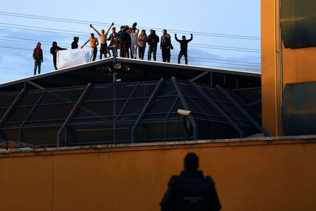 A police officer watching a group of illegal immigrants protesting on the roof of the Aluche Immigration Detention Centre during a riot on March 17, 2020, in Madrid, Spain. PHOTO: AFP