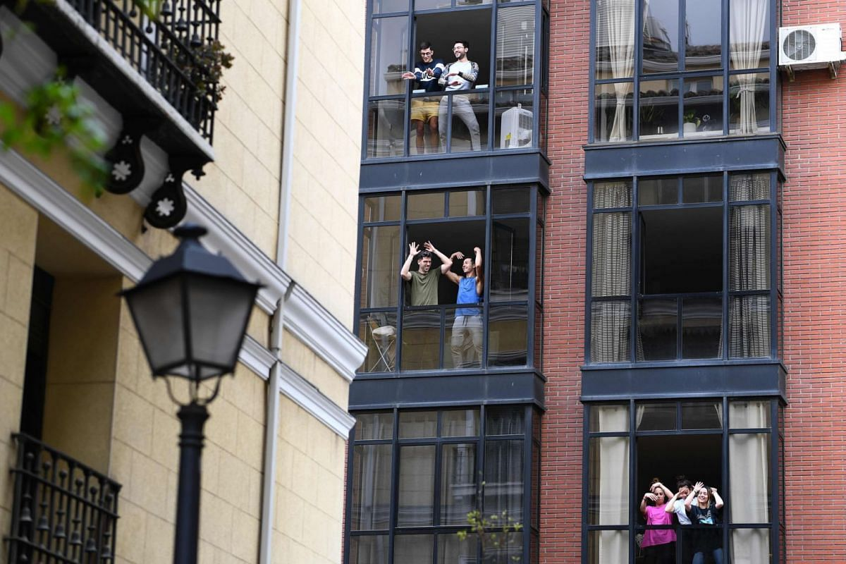 People confined to their homes singing and dancing from their windows to bolster themselves up on March 17, 2020 during a lockdown in Madrid as part of Spain's fight against the spread of the coronavirus. PHOTO: AFP