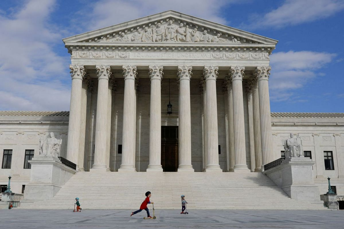 Children riding scooters across the plaza at the United States Supreme Court following the government's notice to halt all building tours on Capitol Hill in Washington on March 17, 2020 to curb the spread of the virus that causes Covid-19. PHOTO: REU