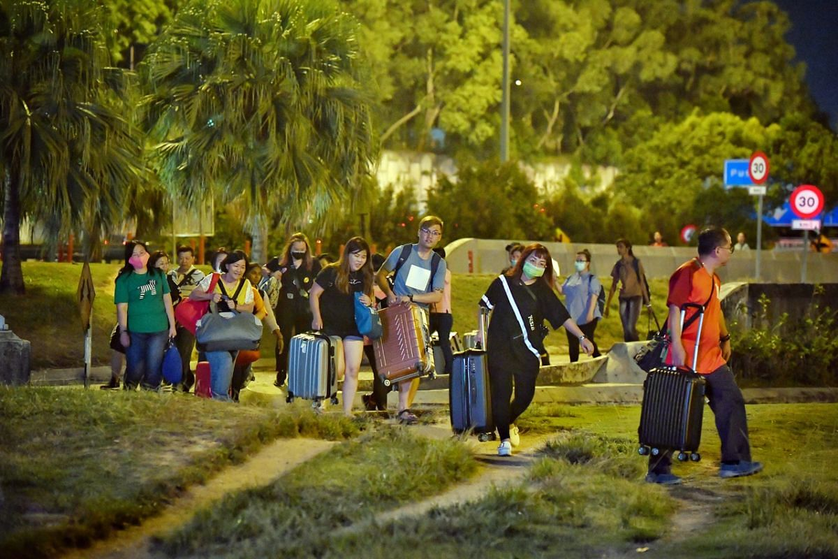 People walking to the Malaysian checkpoint from Johor Baru on March 17, 2020.