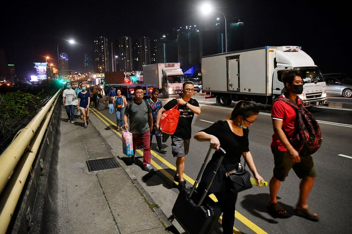 People walking across the Singapore side of the Causeway after clearing the Malaysian checkpoint on March 17, 2020.