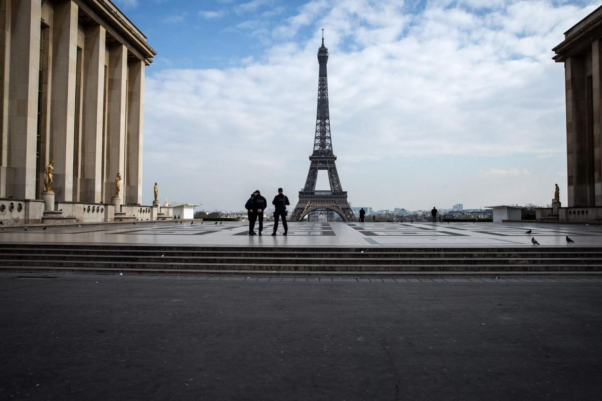Policemen stand on the Trocadero square near the Eiffel Tower in Paris on March on 17, 2020, while a strict lockdown comes into in effect in France to stop the spread of the coronavirus.