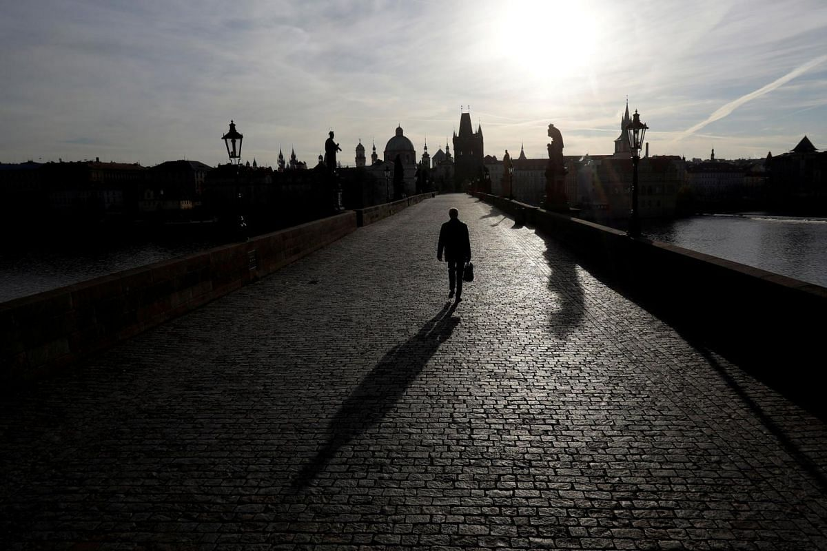 A man walks across an empty medieval Charles Bridge in Prague, as the Czech government restricts movement of people to slow the spread of the coronavirus on March 16, 2020.