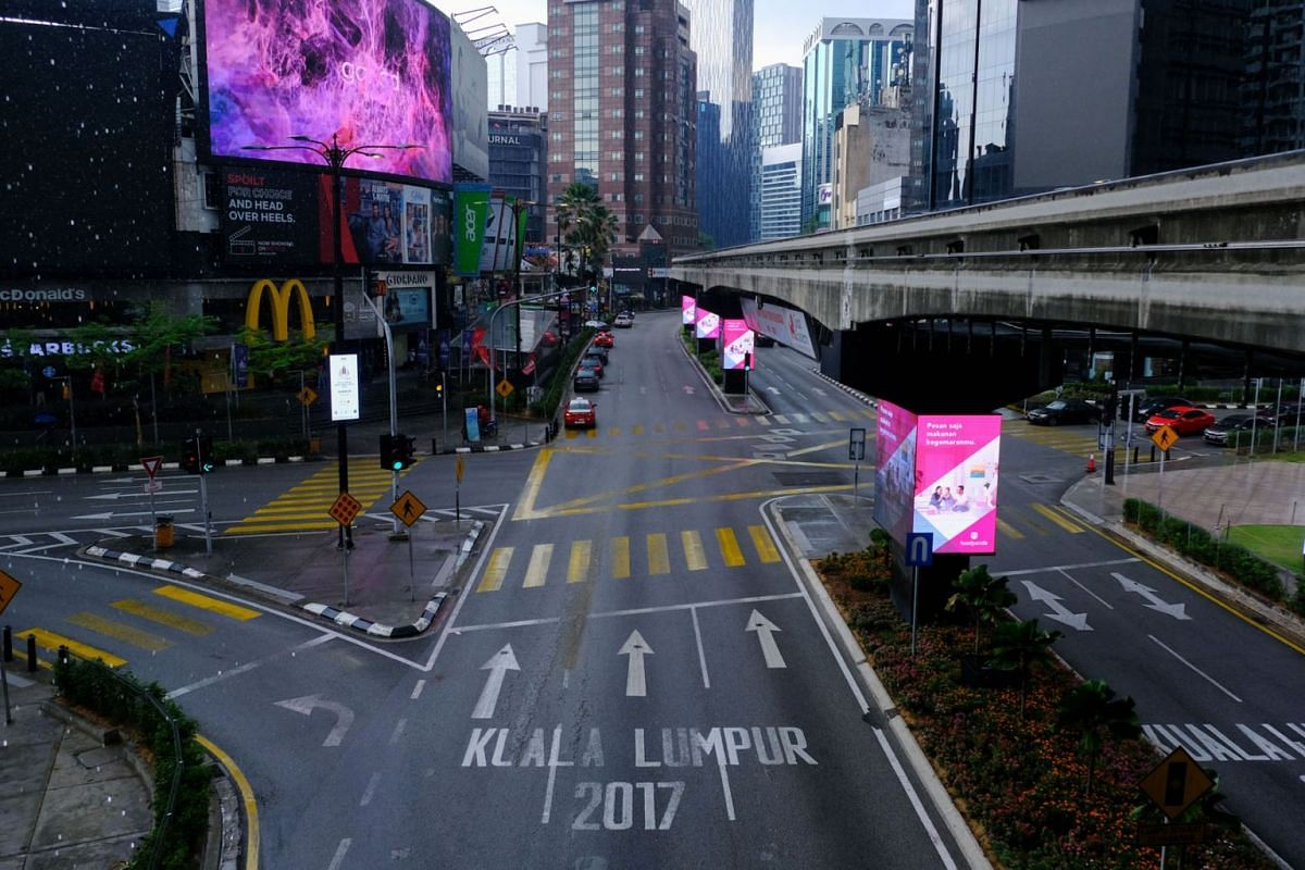Advertising signs stand along an empty highway in the Jalan Bukit Bintang area of Kuala Lumpur, Malaysia, on Wednesday, March 18, 2020, during day one of the lockdown. PHOTO: BLOOMBERG