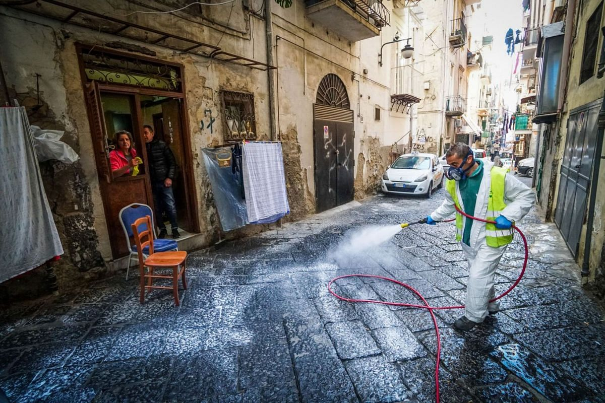 A worker disinfects the street at Quartieri Spagnoli, Naples, Italy, March 18, 2020. According to the latest figures provided by the Civil Protection agency, Italy has recorded 35,713 confirmed coronavirus infections, while the death toll has climbed
