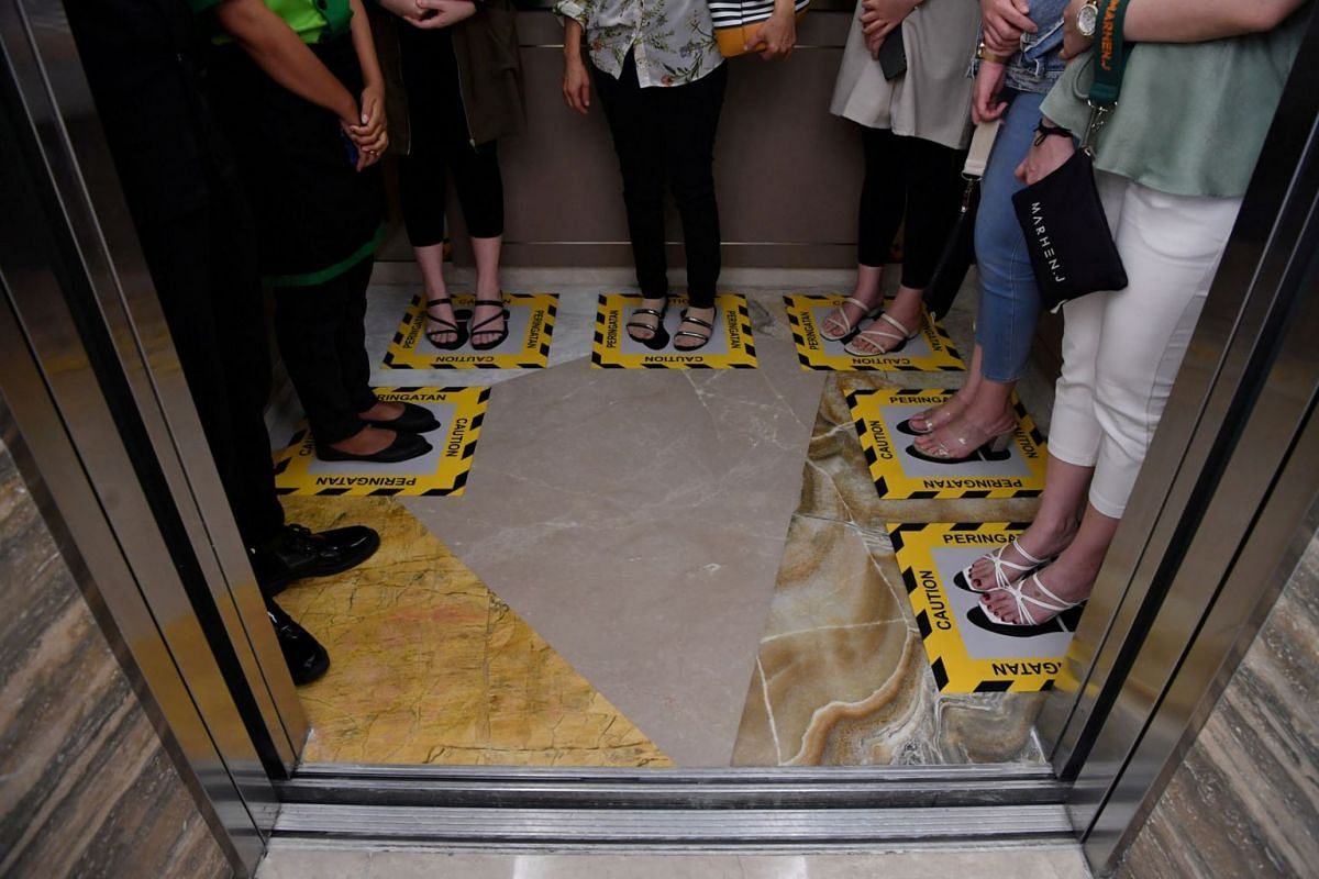 Visitors stand on boxes for social distancing inside an elevator at a shopping mall amid the spread of coronavirus disease (COVID-19) in Surabaya, East Java province, Indonesia, March 18, 2020 in this photo taken by Antara Foto. PHOTO: ANTARA PHOTO V