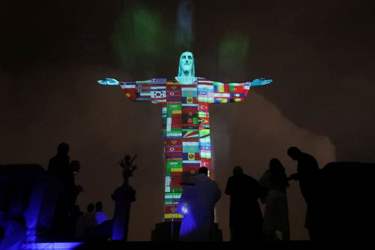 The statue of Christ the Redeemer is lit up in the colors of the countries that are affected by the coronavirus disease (COVID-19) outbreak in Rio de Janeiro, Brazil, March 18, 2020. PHOTO: REUTERS