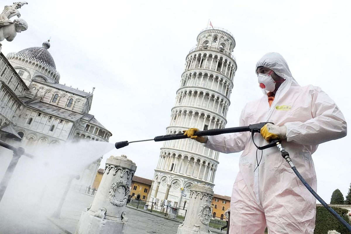 A worker is seen disinfecting the area around the Leaning Tower of Pisa, which is nearly devoid of people, on March 17, 2020.