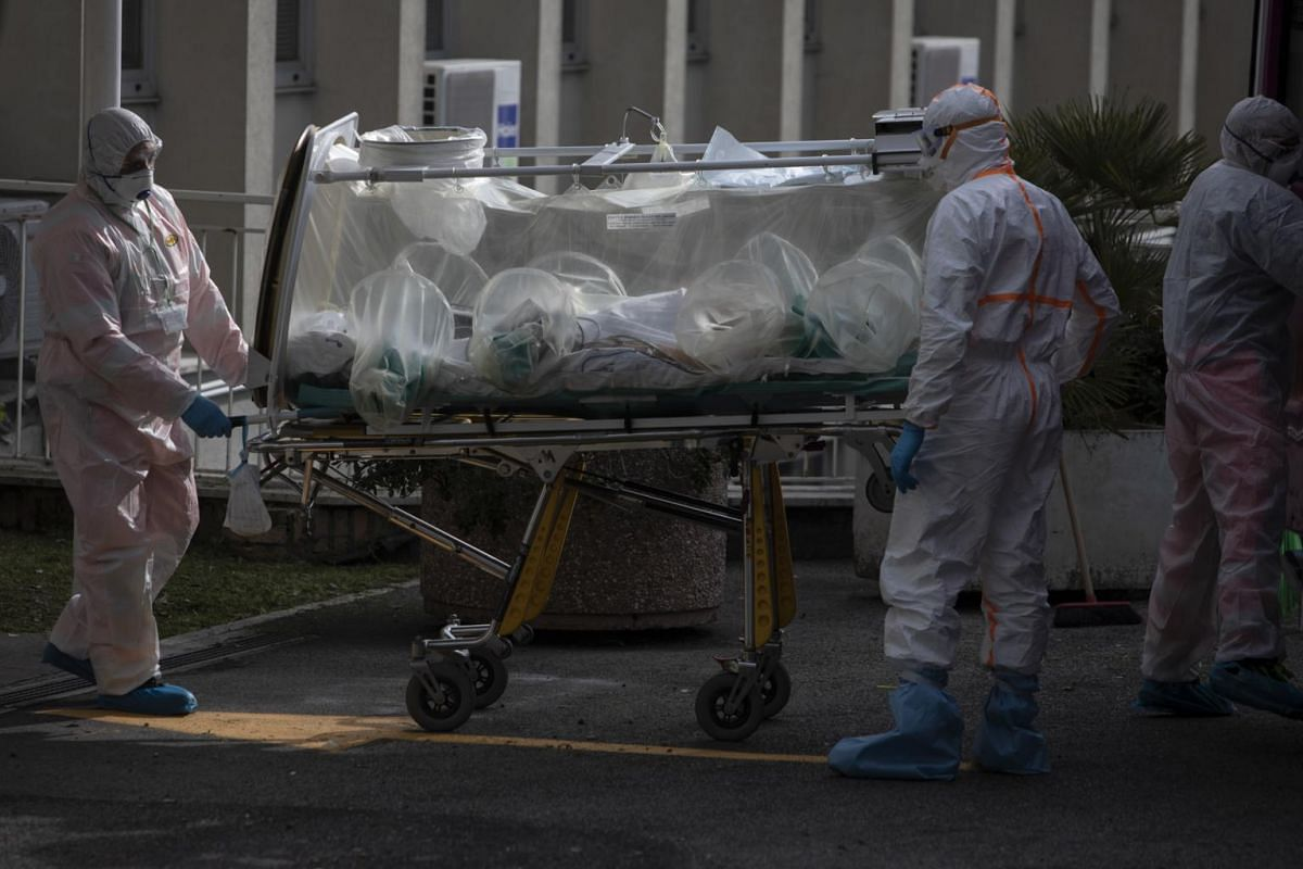 Paramedics transport a patient with the coronavirus at a hospital in Rome on March 17, 2020. Rome's Lazio region has a toll of 32 deaths and 724 infections.