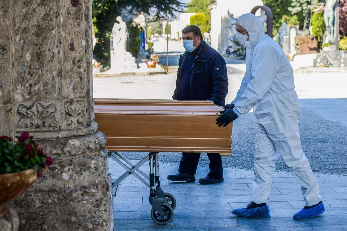 An undertaker wearing a face mask and overalls unloads a coffin out of a hearse on March 16, 2020 at a cemetery in Lombardy, Italy. The nation of 60 million has now recorded 34.2 per cent of all the deaths officially attributed to Covid-19 across the