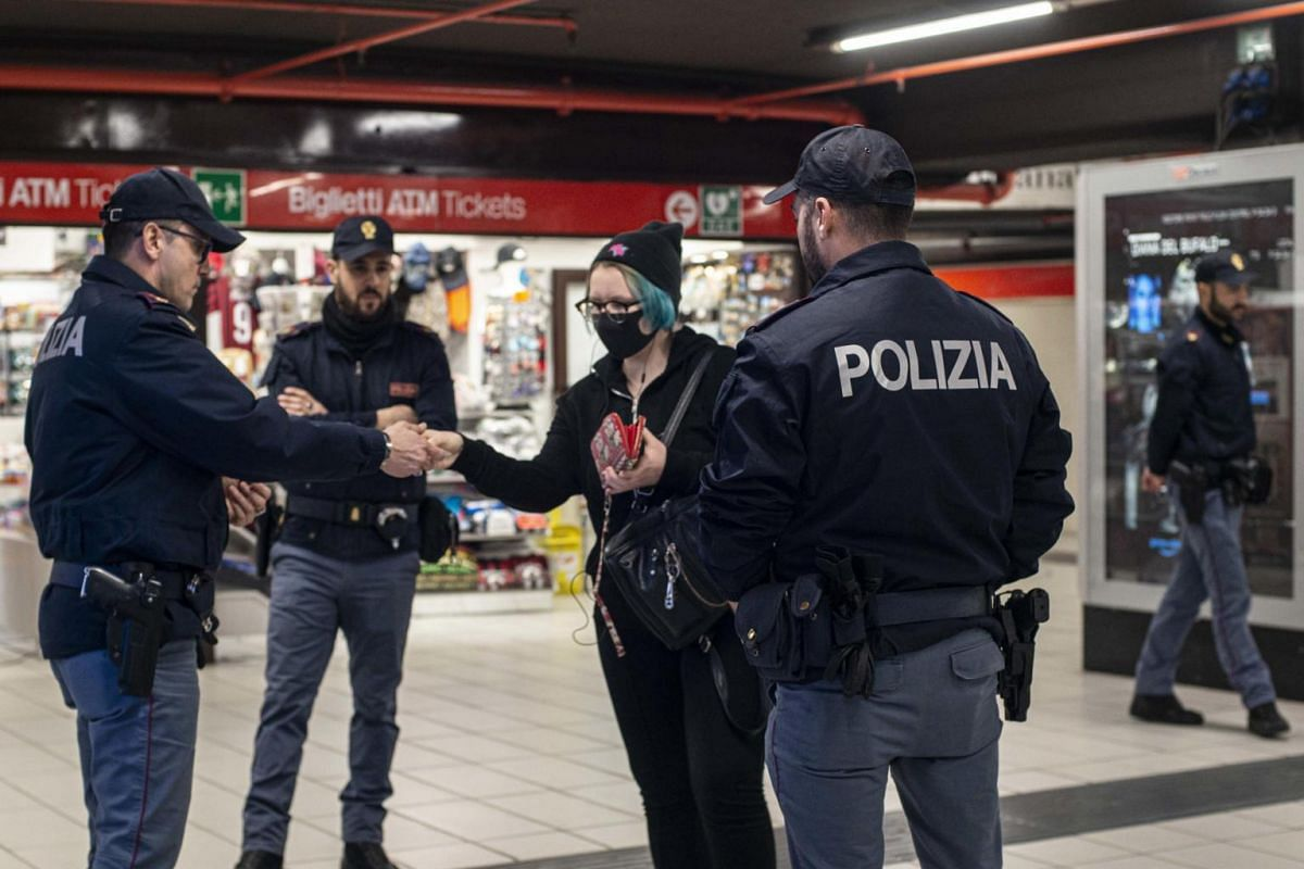 Italian police perform checks in Milan's subway on March 18, 2020.