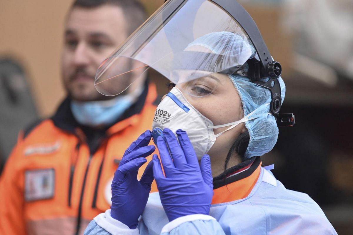 Italian emergency services personnel prepare to recover a patient in Milan on March 18, 2020.