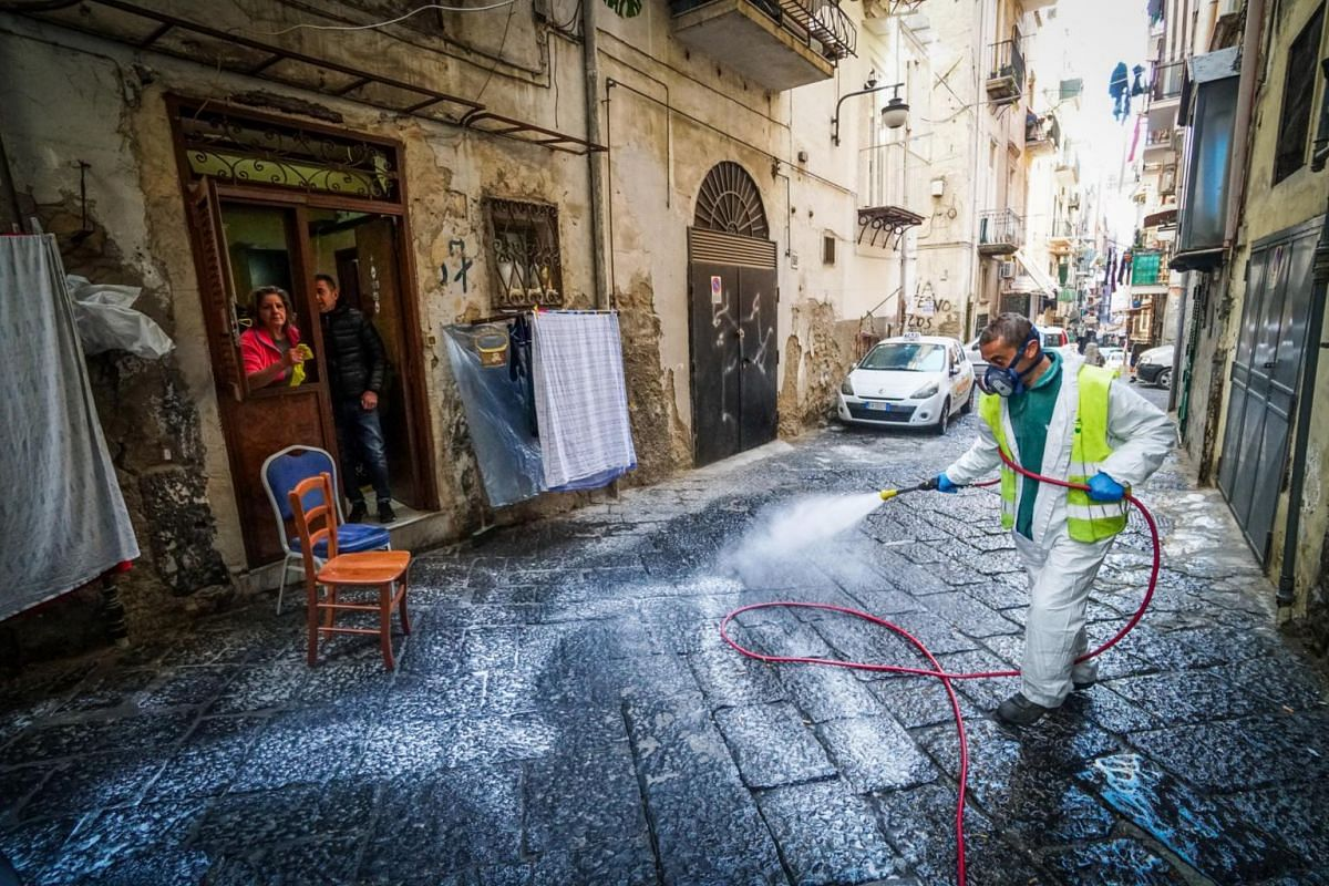 A worker disinfects a street at Quartieri Spagnoli in Naples on March 18, 2020.