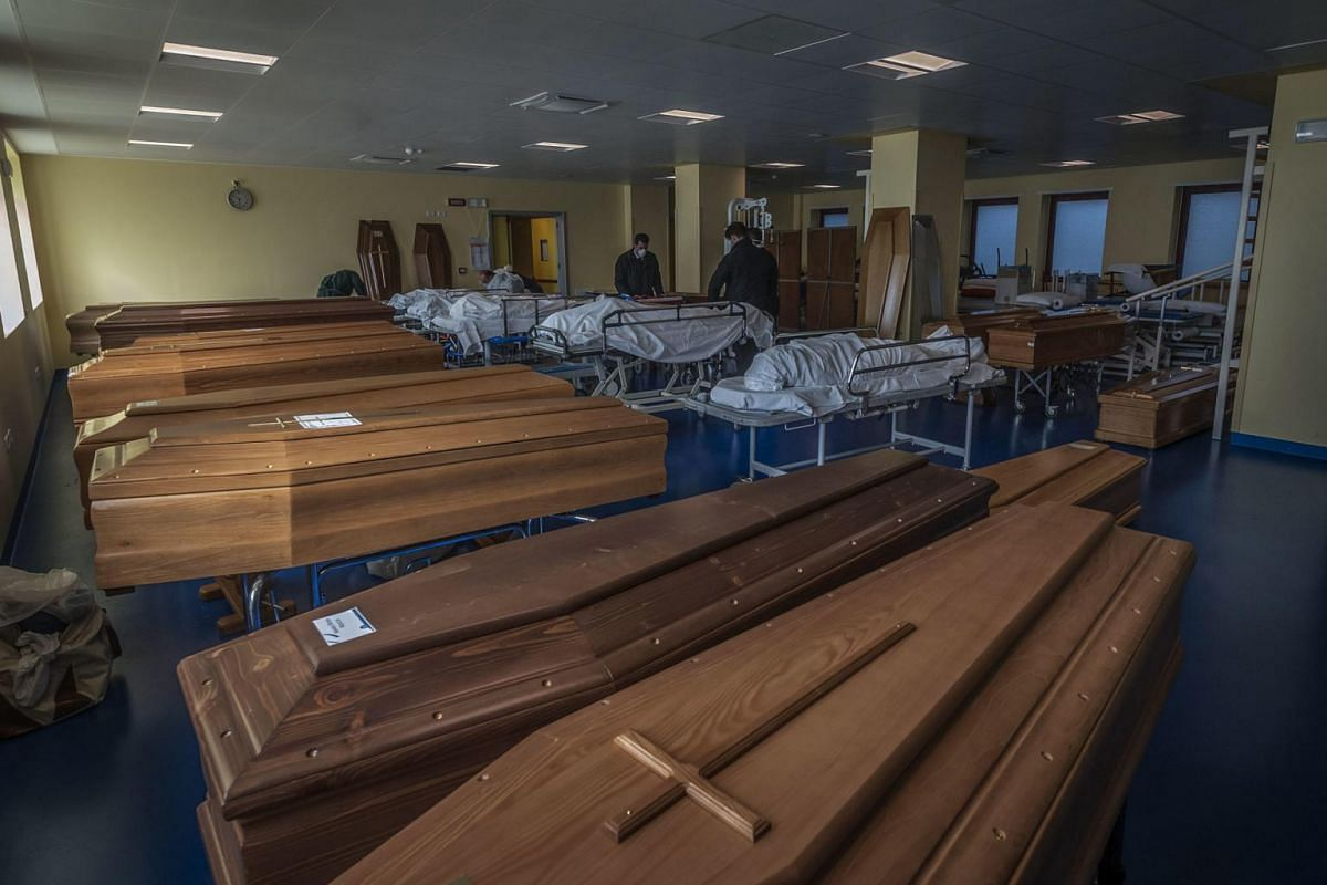 Workers stand next to coffins and remains of the coronavirus victims, in Bergamo, Italy, on March 18, 2020.